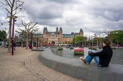 Frau, welche die großen Buchstaben I Amsterdam betrachtet lizenzfreie stockfotos