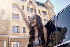 Frau, welche die Hand schaut aus Autofenster heraus anhebt lizenzfreies stockfoto