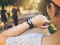 Frau, welche die Herzfrequenz-Übungs-Trainingseignung im Freien überprüft Stockbilder