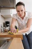 Frau, welche die Küche säubert Stockfoto