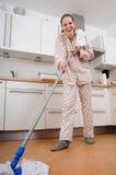Frau, welche die Küche säubert Stockfotografie