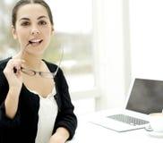 Frau, welche die Kamera beißt auf Brillenarm betrachtet Lizenzfreies Stockbild