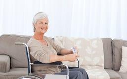 Frau, welche die Kamera in ihrem Rollstuhl betrachtet Stockbilder