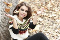 Frau, welche die Kamera spielt mit Blättern betrachtet stockbild