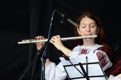 Frau, welche die keltische mittelalterliche Musik der Flöte in der traditionellen schottischen Kleidung spielt Lizenzfreie Stockfotos