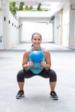Frau, welche die kettlebell Hocke für den Muskel verstärkt Übung tut Stockbild
