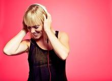 Frau, welche die Musik vom MP3-Player genießt Stockfoto
