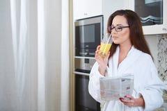 Frau, welche die Nachrichten beim Trinken des Orangensaftes liest lizenzfreie stockfotos