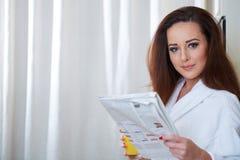 Frau, welche die Nachrichten beim Trinken des Orangensaftes liest stockfotos