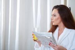 Frau, welche die Nachrichten beim Trinken des Orangensaftes liest stockbilder