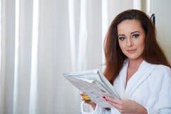 Frau, welche die Nachrichten beim Trinken des Orangensaftes liest lizenzfreies stockfoto