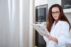 Frau, welche die Nachrichten beim Trinken des Orangensaftes liest lizenzfreie stockfotografie