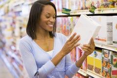 Frau, welche die Nahrungsmittelkennzeichnung im Supermarkt überprüft Lizenzfreies Stockbild
