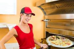 Frau, welche die Pizza im Ofen drückt Lizenzfreies Stockfoto