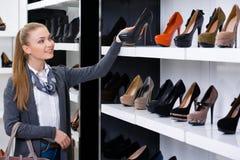 Frau, welche die Reihen von Schuhen betrachtet Stockfoto