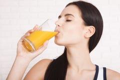 Frau, welche die schöne Mischrasse des Orangensaftes asiatisch, kaukasisches Modell trinkt lizenzfreie stockfotos