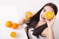 Frau, welche die schöne Mischrasse des Orangensaftes asiatisch, kaukasisches Modell trinkt lizenzfreie stockfotografie