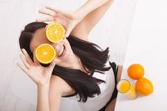 Frau, welche die schöne Mischrasse des Orangensaftes asiatisch, kaukasisches Modell trinkt stockbild