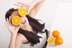 Frau, welche die schöne Mischrasse des Orangensaftes asiatisch, kaukasisches Modell trinkt stockfoto