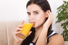 Frau, welche die schöne Mischrasse des Orangensaftes asiatisch, kaukasisches Modell trinkt stockbilder