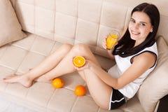 Frau, welche die schöne Mischrasse des Orangensaftes asiatisch, kaukasisches Modell trinkt Ungewöhnlich Draufsicht lizenzfreies stockbild