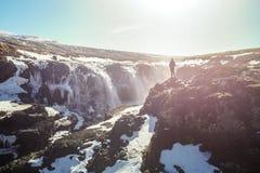 Frau, welche die schöne Schlucht und den Wasserfall Kolugljúfur, in Island genießt stockfoto