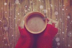 Frau, welche die Schale heiße Kakao oder Kaffee auf hölzernem Hintergrund, Bild tonend hält Lizenzfreies Stockfoto