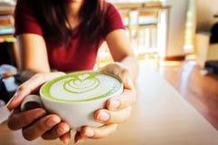 Frau, welche die Schale heißes matcha grünen Tee in ihren Händen, sitzend hält lizenzfreie stockfotos