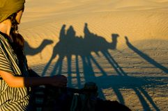 Frau, welche die Schatten während Kamelreiten betrachtet Stockfoto
