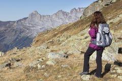 Frau, welche die Schweizer Alpen während des Wanderns im Herbst genießt lizenzfreies stockbild