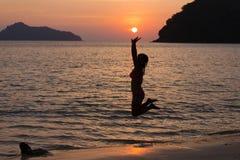 Frau, welche die Sonne erreicht Stockfotos