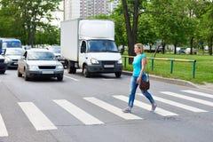 Frau, welche die Straße am Fußgängerübergang kreuzt Stockbilder