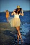Frau, welche die Strandentspannung froh im Sommer durch Ozeanküste genießt Stockfoto