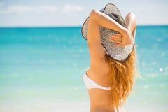 Frau, welche die Strandentspannung froh im Sommer durch tropisches blaues Wasser genießt Lizenzfreies Stockbild