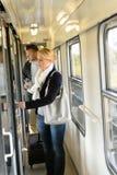 Frau, welche die Tür des Zugabteils öffnet Stockfoto