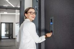 Frau, welche die Tür mit keychain öffnet stockfoto