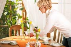 Frau, welche die Tabelle für Tee der Kaffeezeit einstellt Stockbilder