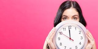 Frau, welche die Uhr zeigt fast 12 hält Stockbilder