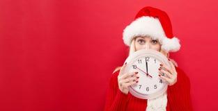Frau, welche die Uhr zeigt fast 12 hält Lizenzfreies Stockfoto