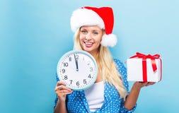 Frau, welche die Uhr zeigt fast 12 hält Lizenzfreie Stockbilder