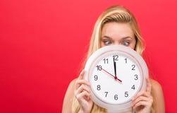 Frau, welche die Uhr zeigt fast 12 hält Lizenzfreies Stockbild