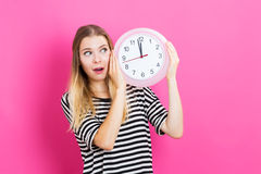 Frau, welche die Uhr zeigt fast 12 hält Lizenzfreie Stockfotografie