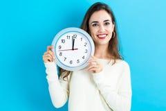 Frau, welche die Uhr zeigt fast 12 hält Lizenzfreie Stockfotos