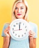 Frau, welche die Uhr zeigt fast 12 hält Stockfotos