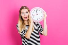 Frau, welche die Uhr zeigt fast 12 hält Stockfoto