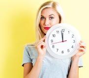 Frau, welche die Uhr zeigt fast 12 hält Stockbild