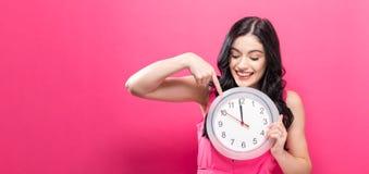 Frau, welche die Uhr zeigt fast 12 hält Stockfotografie
