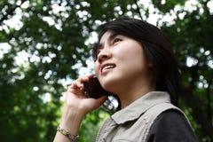 Frau, welche die Unterhaltung auf einem Handy genießt Stockfotografie