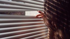 Frau, welche die Vorhänge von Hand eindrückt und heraus Fenster schaut stock video footage