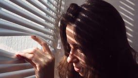 Frau, welche die Vorhänge von Hand eindrückt und heraus Fenster schaut stock video
